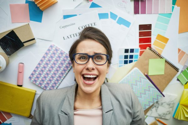 Top view portrait of contemporary businesswoman wearing glasses smiling and lying over  art and design supplies, copy space